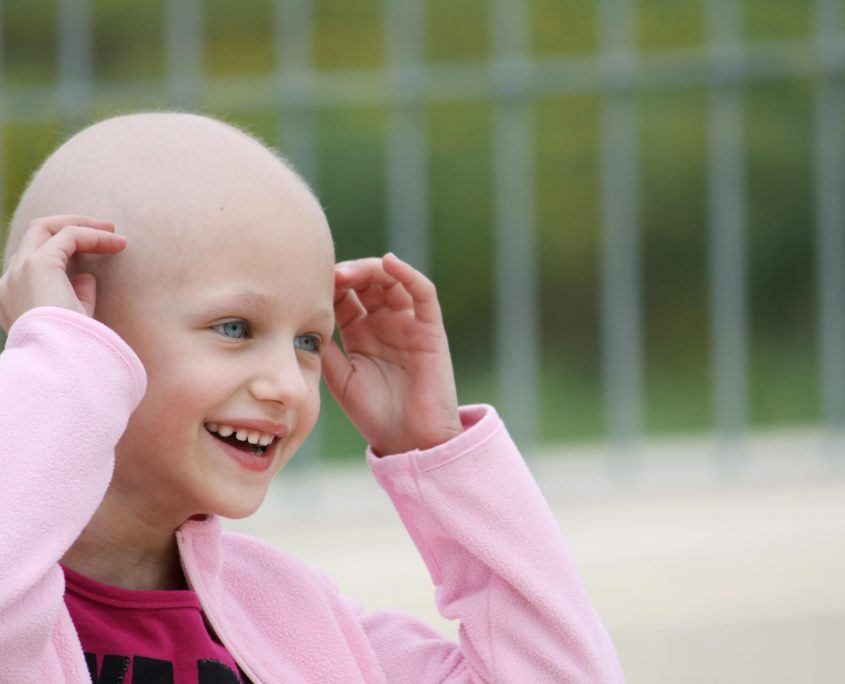 Little girl wins the war on cancer and smiles victoriously