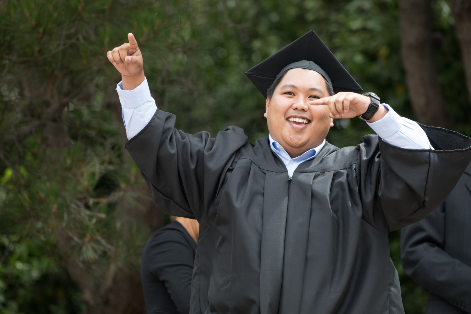 Happy Graduate pointing to Friends