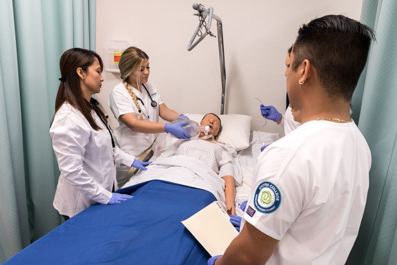 Diverse group of students practicing nursing skills on a simulation mannequin.