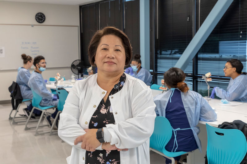 Dental assistant instructor wearing a white lab coat with students around a table in the background