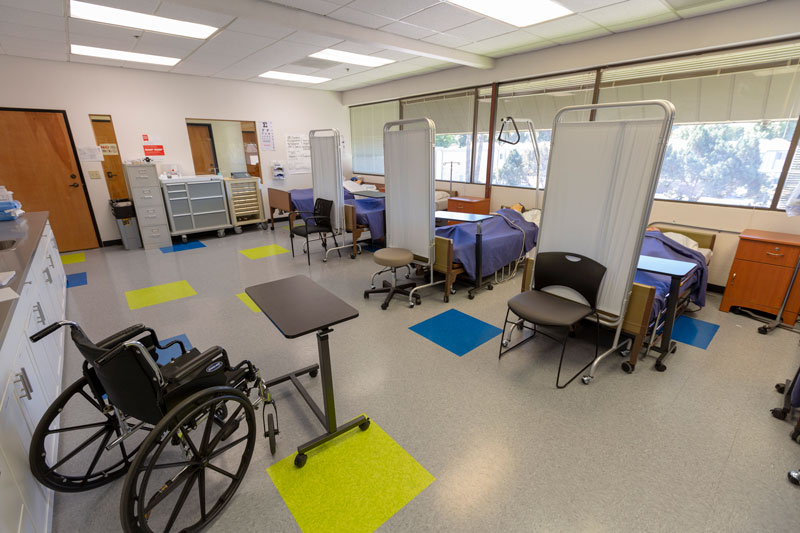 View of a simulation lab with four beds, four simulation mannequins, and a wheelchair.