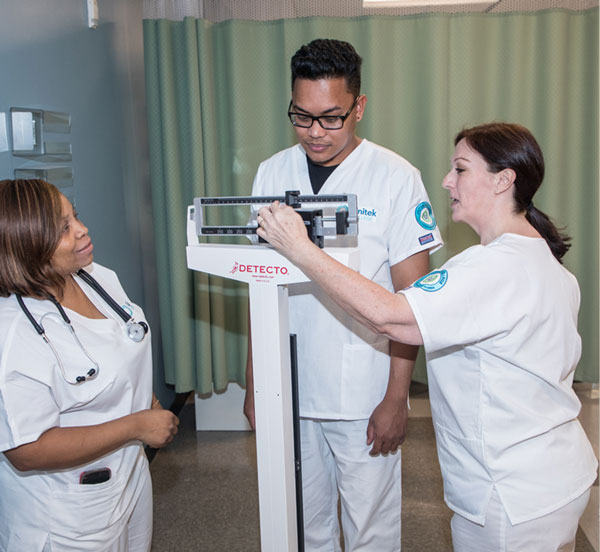 Nurses practicing using a scale to measure patient's weight