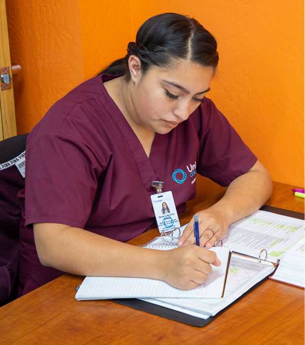 Nursing student taking notes in notebook