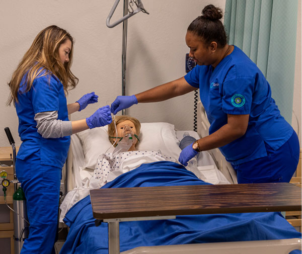 Nursing students practicing on simulation mannequin