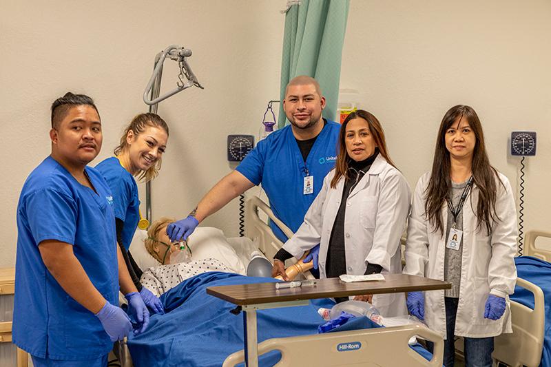 Students practicing nursing skills on a simulation mannequin