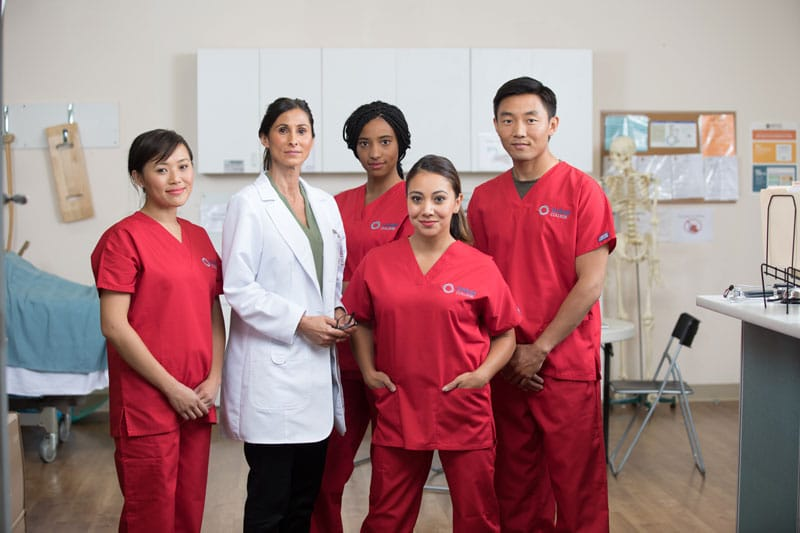 Four students in red scrubs standing with their instructor.