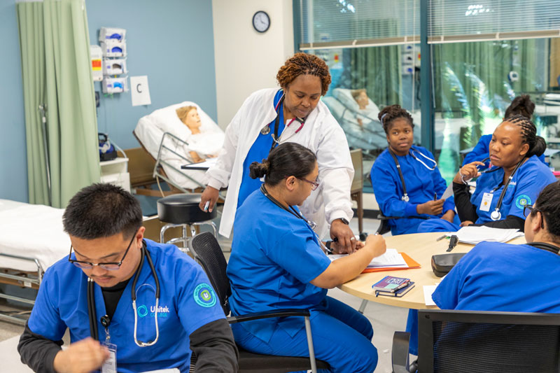 Nursing students learning from their instructor and taking notes in a simulation lab