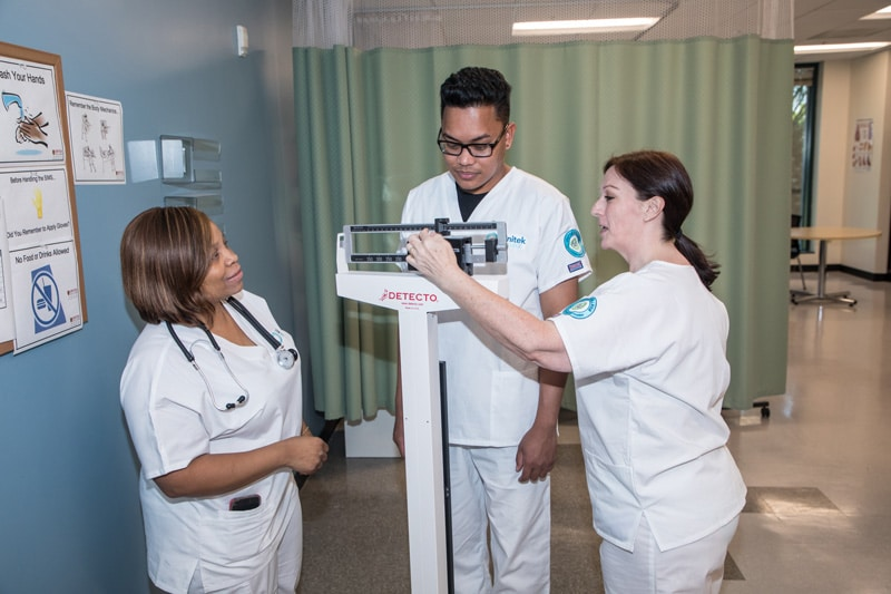Nursing student practicing using a scale to measure another student's weight