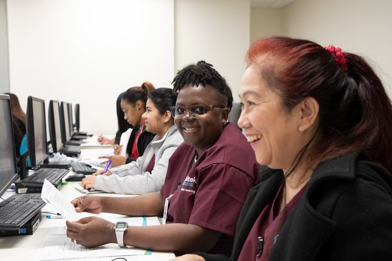Diverse group of students laughing and studying in a computer lab.