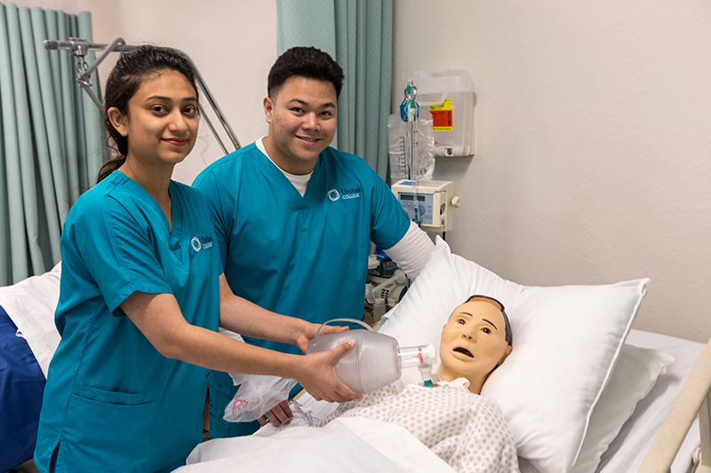 Two nursing students smiling with simulation mannequin