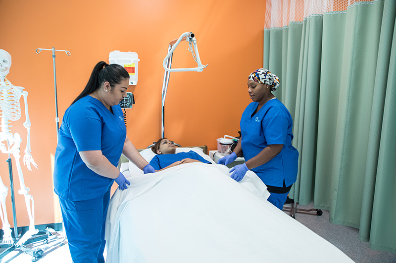 Nursing students practicing nursing skills on each other in simulation lab.