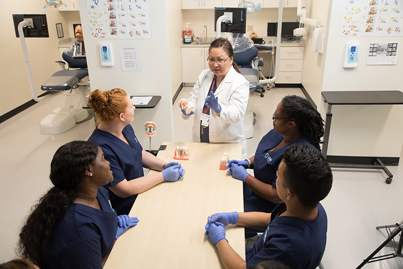 Dental assistant instructor teaching a group of students