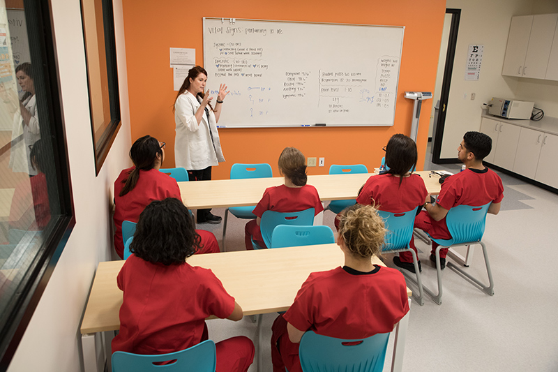 Nursing students sitting in a classroom listening to their instructor giving a lecture