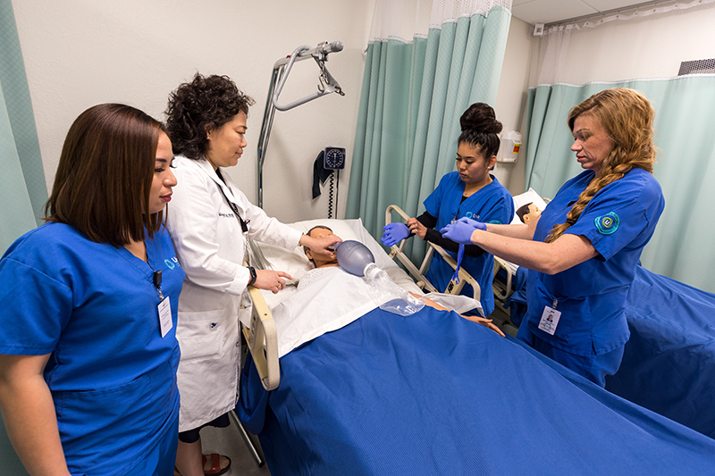 Students practicing nursing skills on a simulation mannequin