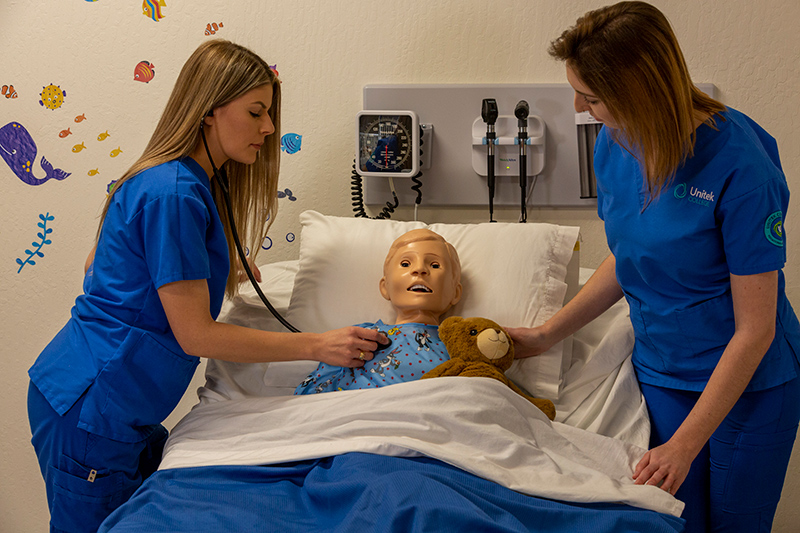 Students practicing nursing skills on a child simulation mannequin