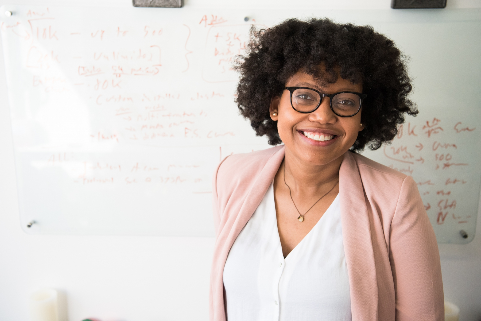 Smiling woman in front of a whiteboard