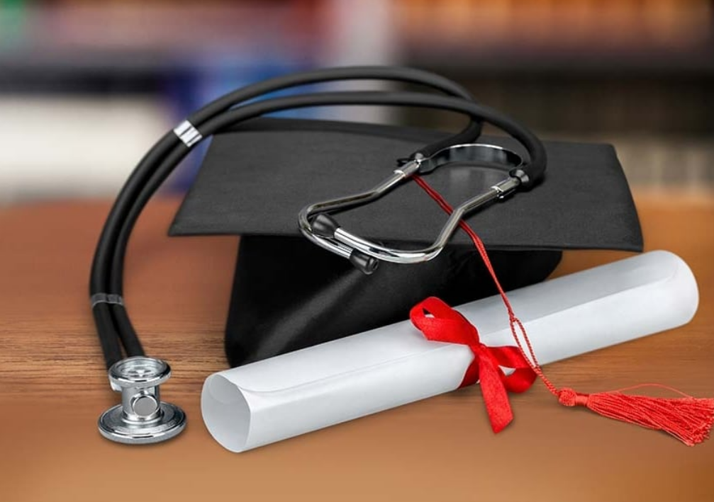 Graduation cap with diploma and stethoscope